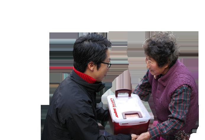 젊은 남자가 할머니께 김치통을 전달하고 있다